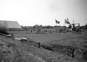 Dutch Farm with Three European Flags on Display and Windmill