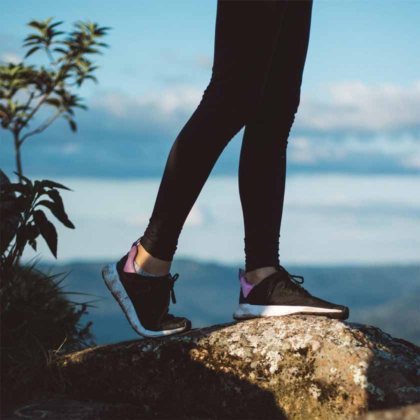woman wearing gym leggings stood on a rock