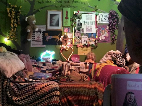 Jackie's front room, featuring a sofa with multicoloured throw and a wall covered in lights, posters and art