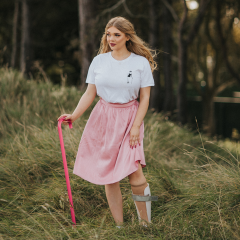 A woman with long, blonde hair stands on a grassy embankment, wearing a white t-shirt and pink floaty dress, holding a pink walking stick