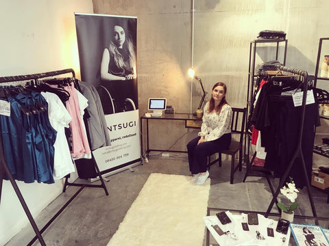 Emma sitting in her popup shop space next to a desk, roller banner and two rails of clothing