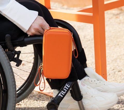 An image of a wheelchair user's legs and close up of an orange bag attached to the chair