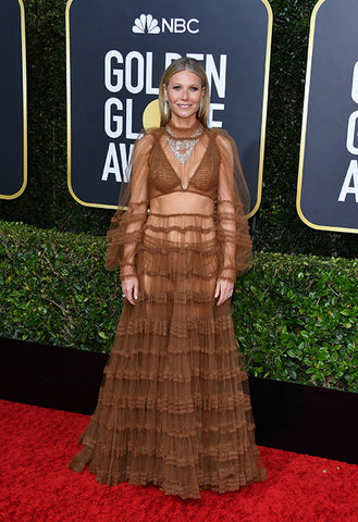 Gwyneth Paltrow on the red carpet, wearing a brown, layered tulle dress