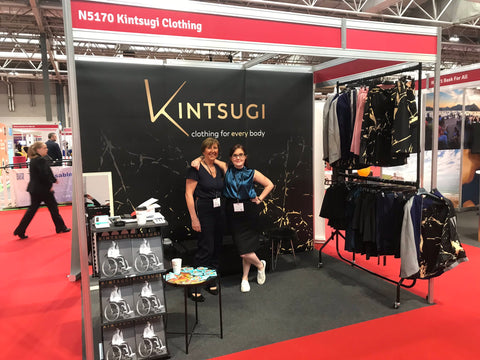 Emma and her mum stand in front of Kintsugi's stand and Naidex. Emma has her arm around her mother's shoulder.
