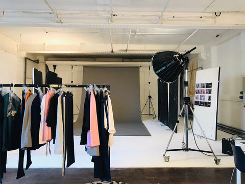 A photography studio with a clothing rail in the foreground