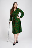 A tall model with long dark hair and a glittery walking stick wearing a green midi dress with long sleeves and orange and black animal print pattern