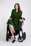 A tall model with long dark hair, sitting in her chair with her legs crossed, wearing the green animal print midi dress