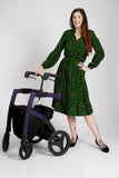 A tall model with long dark hair wearing a green animal print midi dress, standing next to her rollator with one hand on it and the other on her waist