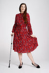 A tall model with long dark hair and a glittery walking stick wearing a red midi dress with long sleeves and white and a black animal print pattern