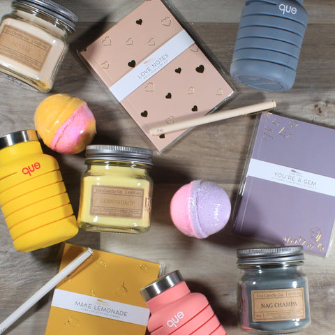 Assorted items in yellow, pink, purple and grey, arrange sporadically over a wood background