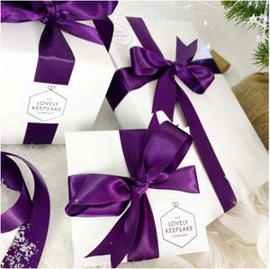"A range of white ""Lovely Keepsake Company"" presentation boxes, with purple ribbon and logo."