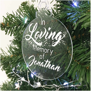 Exclusive to 'The Lovely Gift Group'. A bauble shaped 'In Loving Memory Of' Christmas tree ornament. Clear acrylic with white text. Side angle.