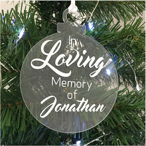 Exclusive to 'The Lovely Gift Group'. A bauble shaped 'In Loving Memory Of' Christmas tree ornament. Clear acrylic with white text. Alternative angle.