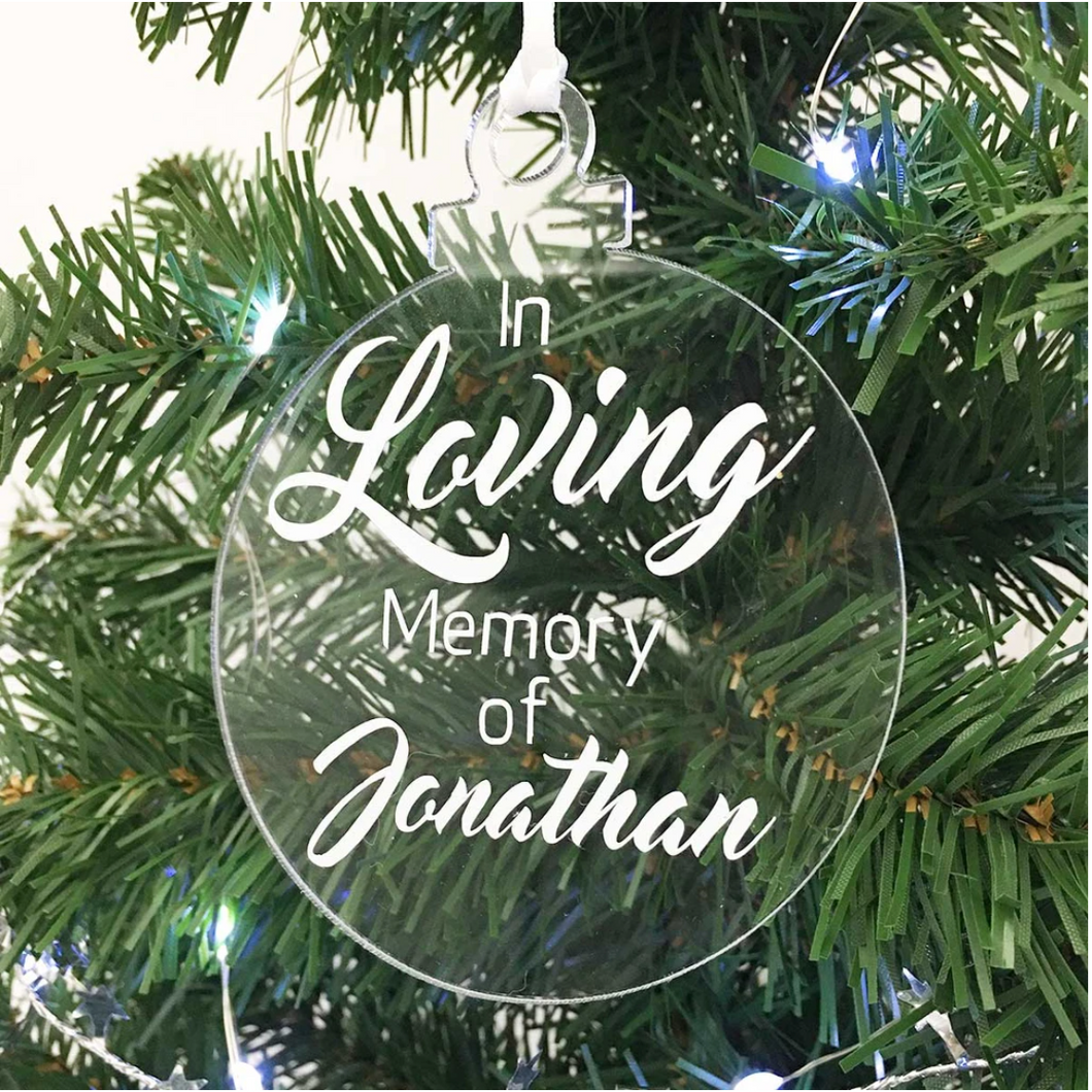 Exclusive to 'The Lovely Gift Group'. A bauble shaped 'In Loving Memory Of' Christmas tree ornament. Clear acrylic with white text.
