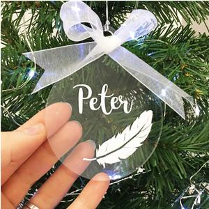 Personalised Memorial Christmas Tree Decoration, Clear Acrylic Hanging Bauble, White Feather and Name. Alternative view - hand presents.