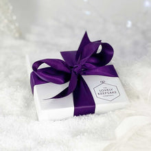 "Load image into Gallery viewer, Flattish white ""Lovely Keepsake Company"" presentation box, with purple ribbon and logo."
