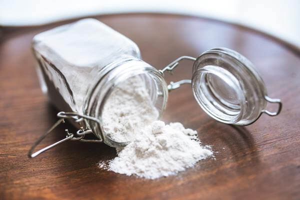 white powder pouring out of a clear jar close up view