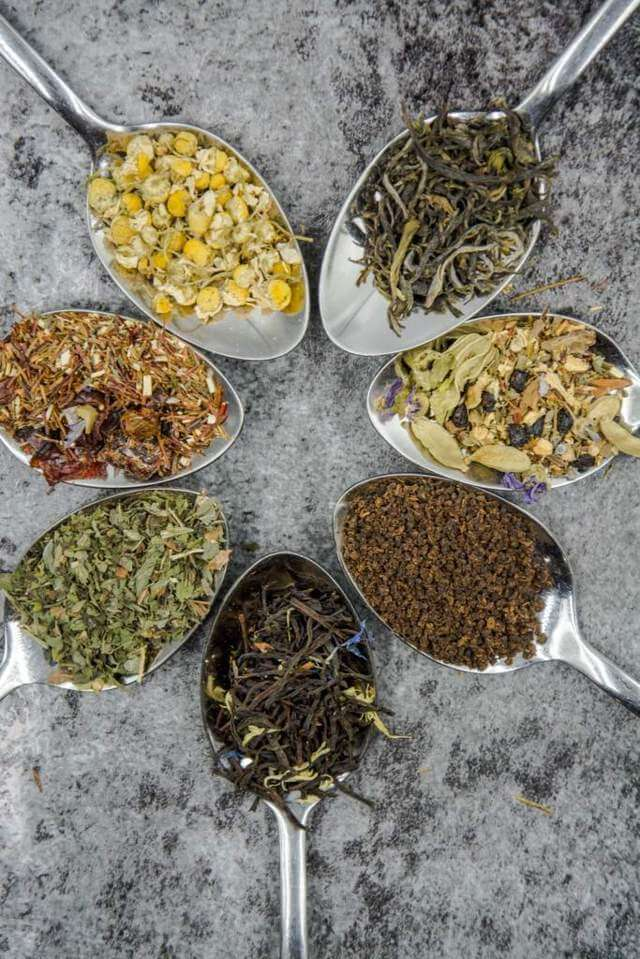 assorted loose tea leaves placed on spoons top view