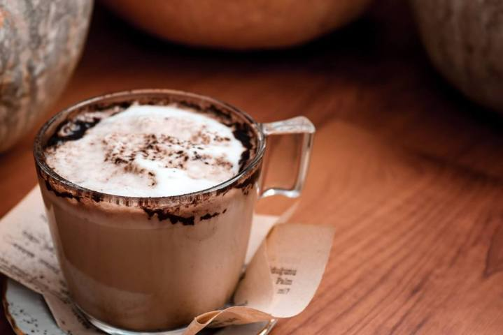 clear mug of chocolate drink with white froth