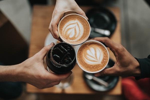 hands doing cheers with different kinds of coffee