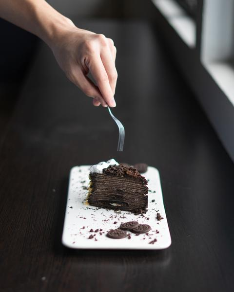 hand holding a fork to grab a piece from a chocolate cake
