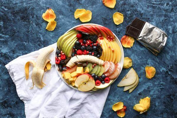 plate full of fruits berries bananas apples top view on a blue background