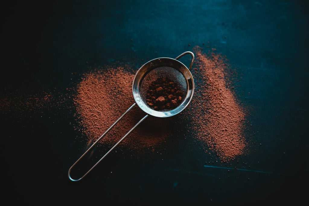 cocoa powder on a silver mini strainer top view