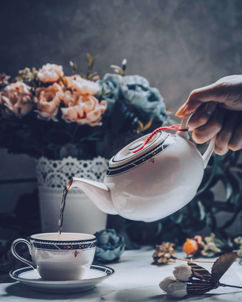 hand pouring tea from tea pot to tea cup