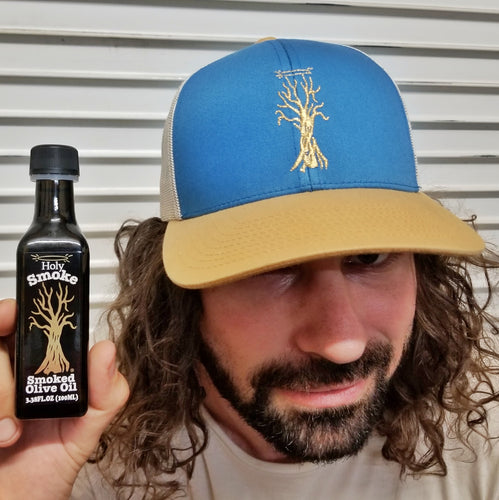 a doofus wearing a blue hat and holding a bottle of smoked olive oil