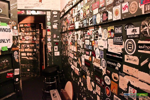 backstage in band prep room at a venue - wall covered in band stickers