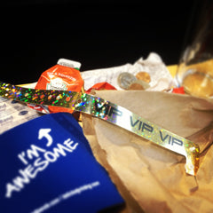 gold vip holographic plastic wristband, blue koozie, and packet of ketchup with some pocket change in the background