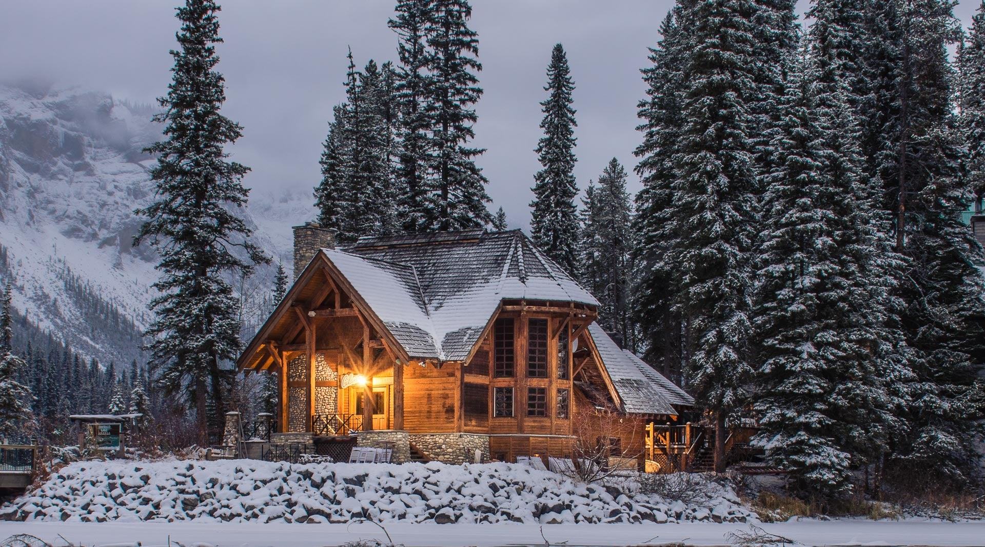 Wooden House Surrounded by Trees and Snowy Mountains in Winter