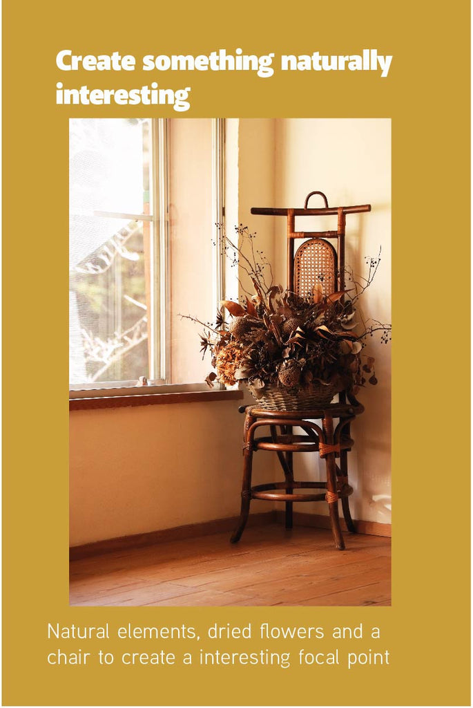 A corner with a chair and a basket of dried flowers