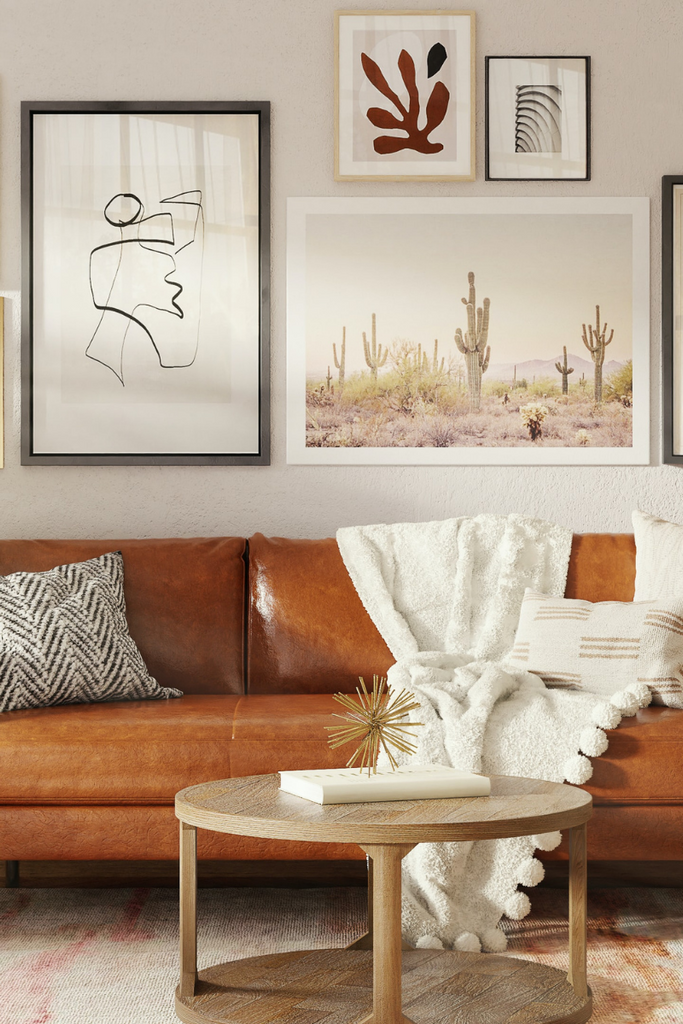 A living room view with a brown leather sofa in the centre with wall prints on the wall and a throw pillows and a throw blanket on the sofa