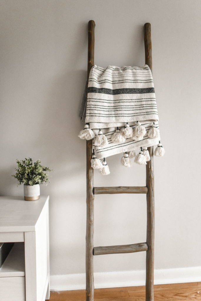 A brown wooden leaning ladder next to a white desk with a plant on top of it and a throw blanket on the ladder