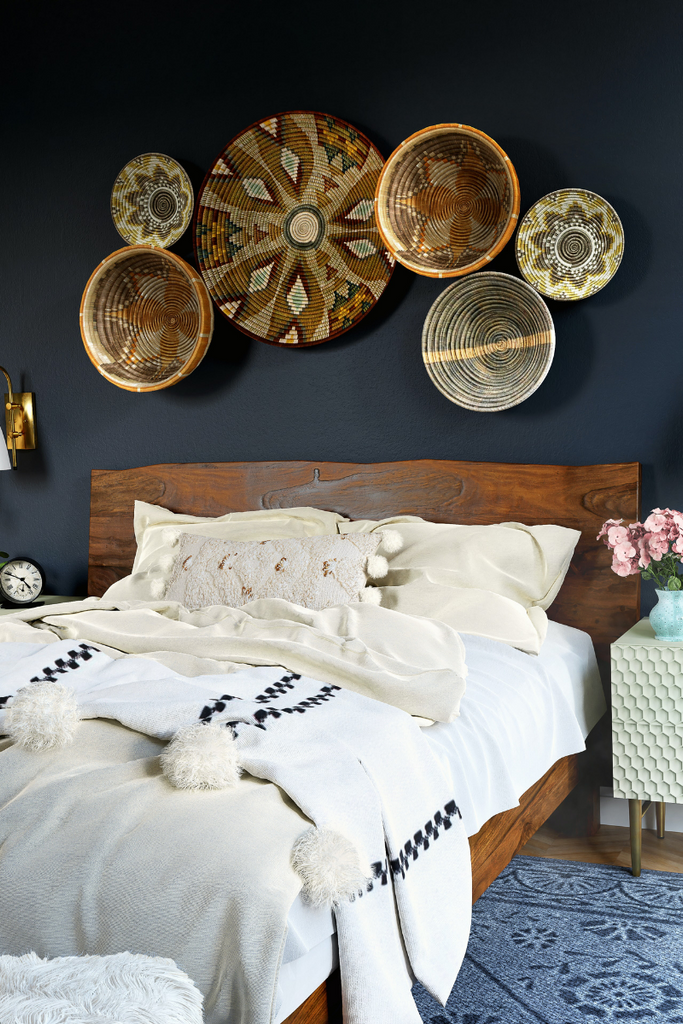a bedroom view with an assortments of baskets on the wall and a throw blanket at the foot of the bed