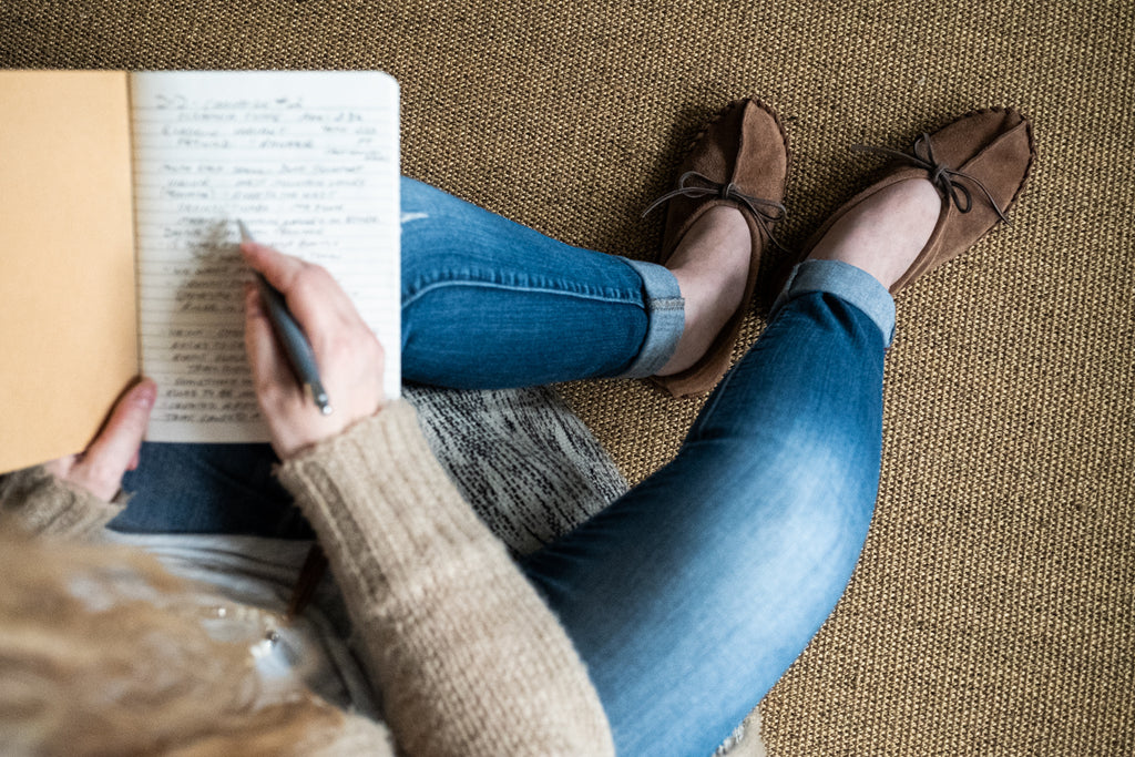 woman journaling in cozy moccasins fall