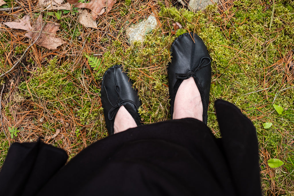 Black ballet moccasins looking down on mossy surface forest barefoot earthing