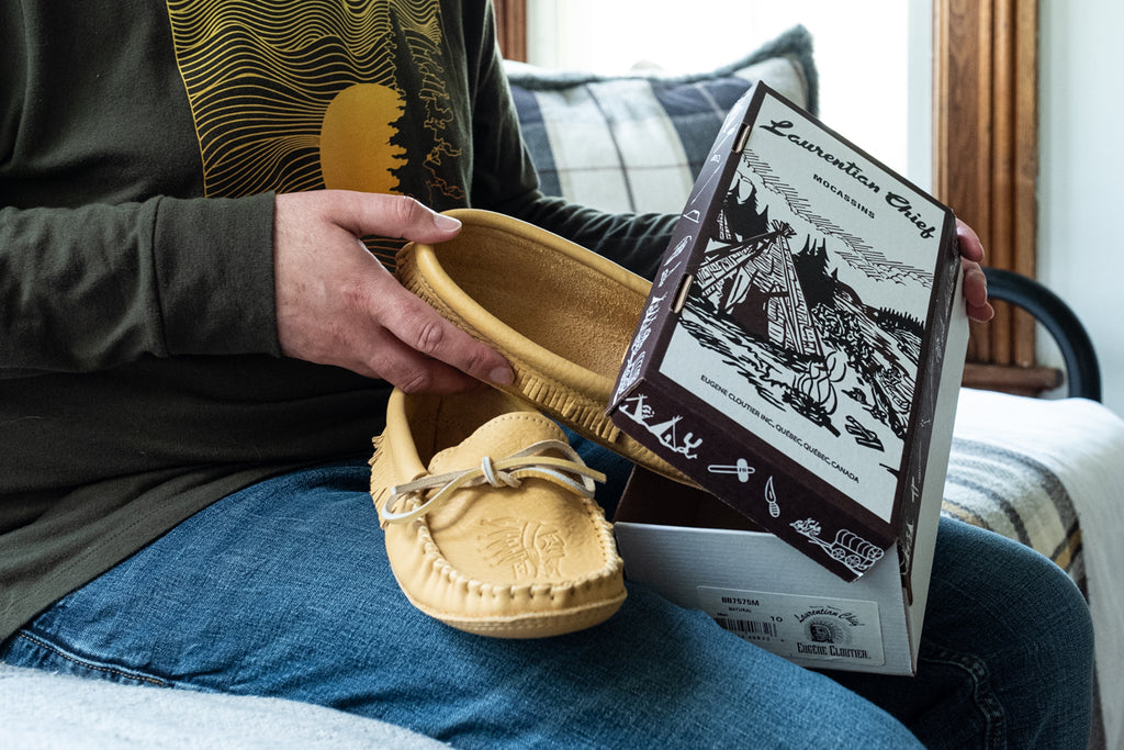 opening a box of men's Laurentian Chief Canadian moccasins
