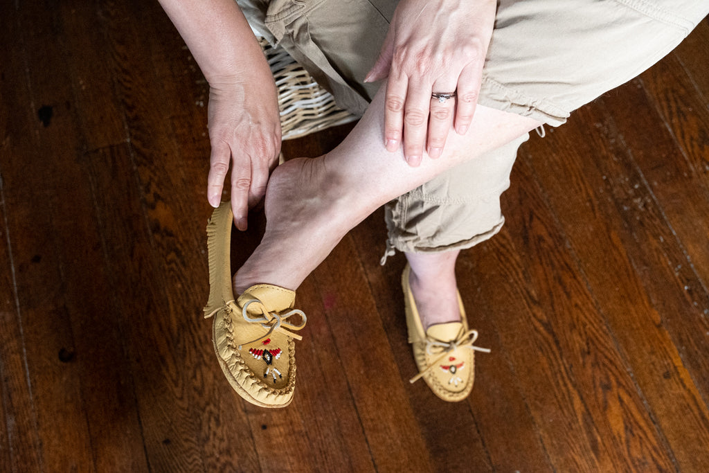 trying on a pair of women's Laurentian Chief beaded moccasin slippers