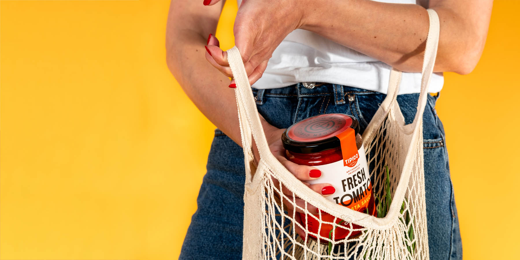 Woman holding shopping bag, taking out a jar of Tipico sauce