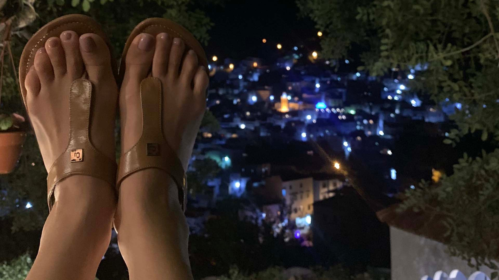 Tan colored grounding sandals up in the air with blue street lights in the distance