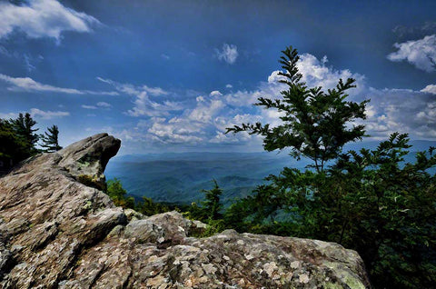 The Blowing Rock from North Carolina and the majestic mountains beyond.  A storm is coming in but there are still white clouds in the sky.   Blowing Rock by Alison Thomas of Serenity Scenes Photography and Digital Art.
