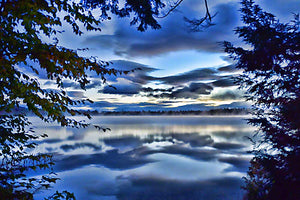 Tree branches frame blue sky and clouds with a hint of sunrise reflected in a cool mountain lake.  Clouds in the Lake by Alison Thomas of Serenity Scenes Photography and Digital Art.