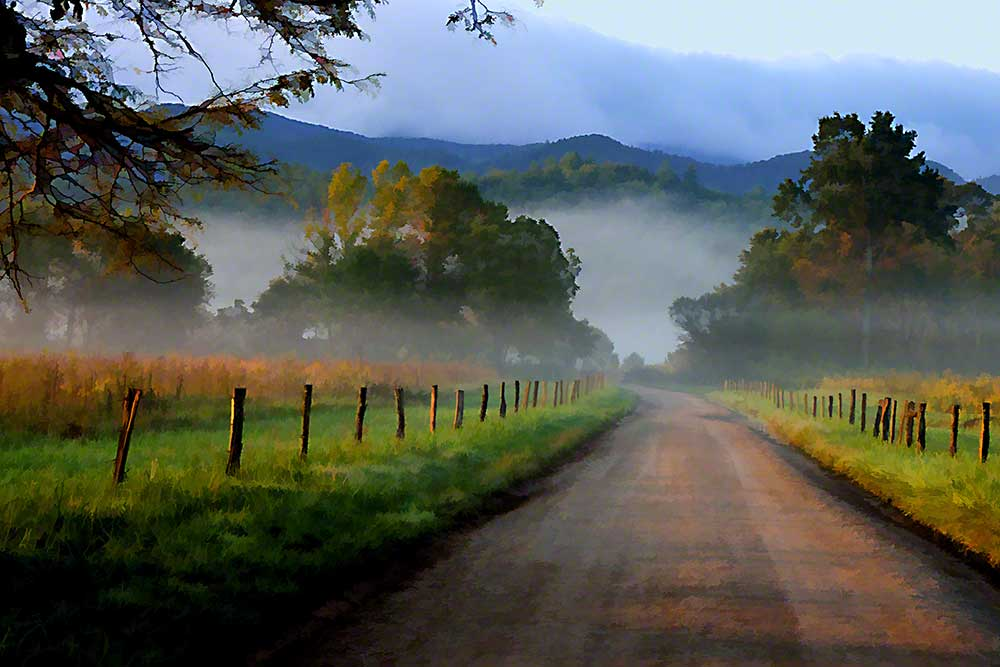 A dirt road bordered by a rustic fence travels into the mountains and the fog nestled among them.  Into the Fog by Alison Thomas of Serenity Scenes Photography and Digital Art.