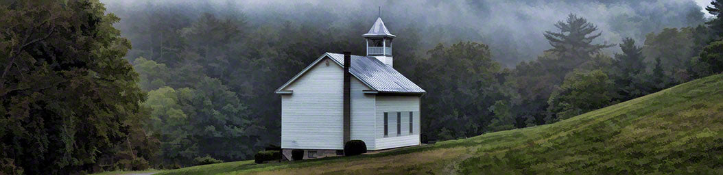 A little white church stands alone in a meadow, nestled in a green forest woven through with fog.  Little White Church by Alison Thomas of Serenity Scenes Photography and Digital Art.