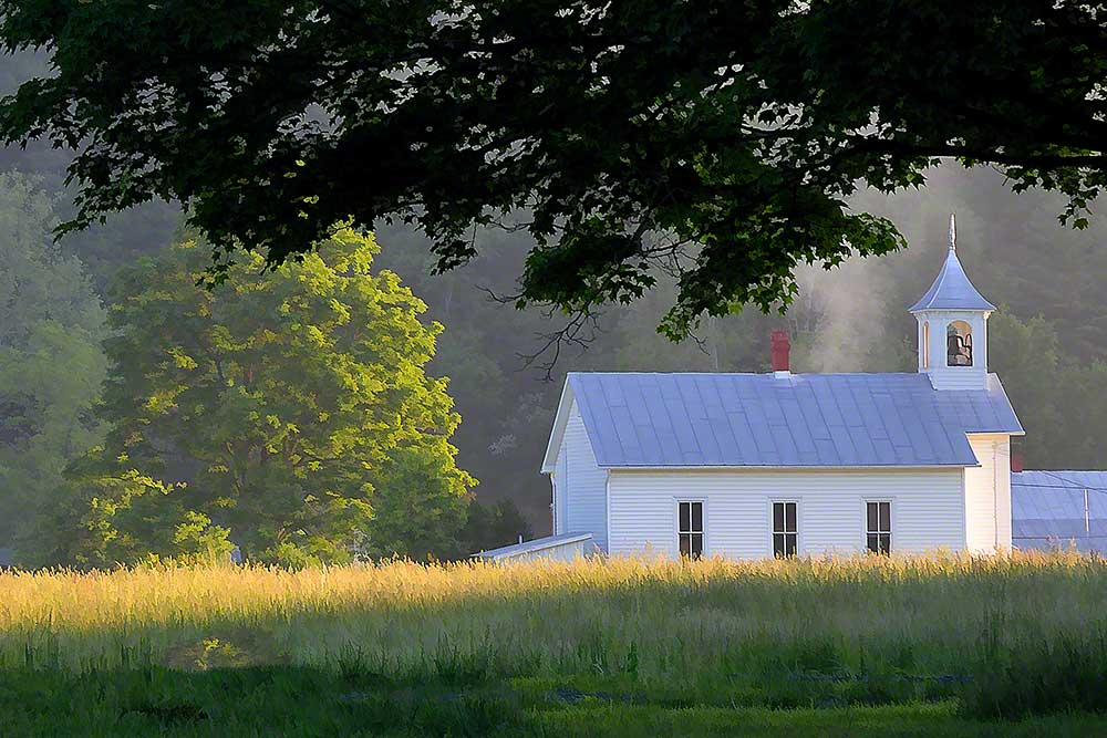 The morning sun shines through the steeple of a white country church accompanied by a wisp of fog.   The grass picks up the light which shelters the church.  Perfect Light by Alison Thomas of Serenity Scenes Photography and Digital Art.