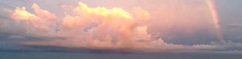 Fluffy cumulus clouds illuminated in the soft pink light of sunset. Off to the side a small rainbow emerges. Sunset Clouds by Alison Thomas of Serenity Scenes Photography and Digital Art.