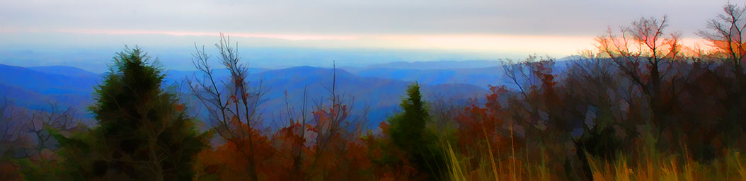 The sun is setting over the mountains in late fall.  The pink sky and blue mountains can be seen through the foliage at the edge of the tallest mountain in the area.  Top of the Mountain by Alison Thomas of Serenity Scenes Photography and Digital Art.