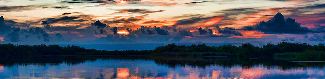 A sunrise over the wetlands paints the sky bright oranges and reds behind heavy clouds. The rippling water reflects these bright colors and the dark green vegetation surrounding it.  Wetlands Sunrise by Alison Thomas of Serenity Scenes Photography and Digital Art